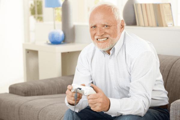 Пожилой человек играет в компьютерную игру